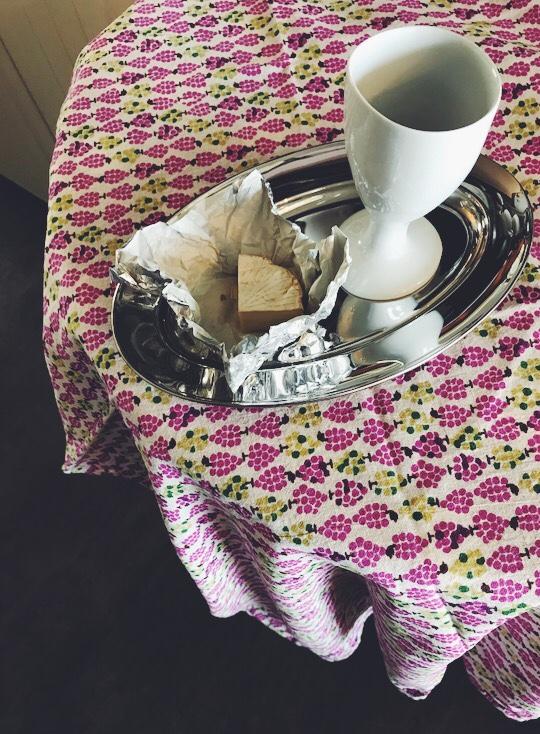 テーブルの上のシルバーのお皿とグラスとチーズ