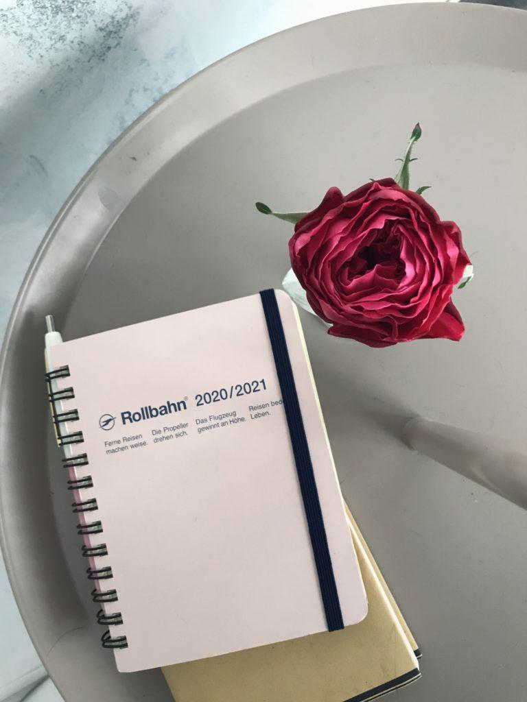 HAYテーブルの上にバラと手帳ロルバーン