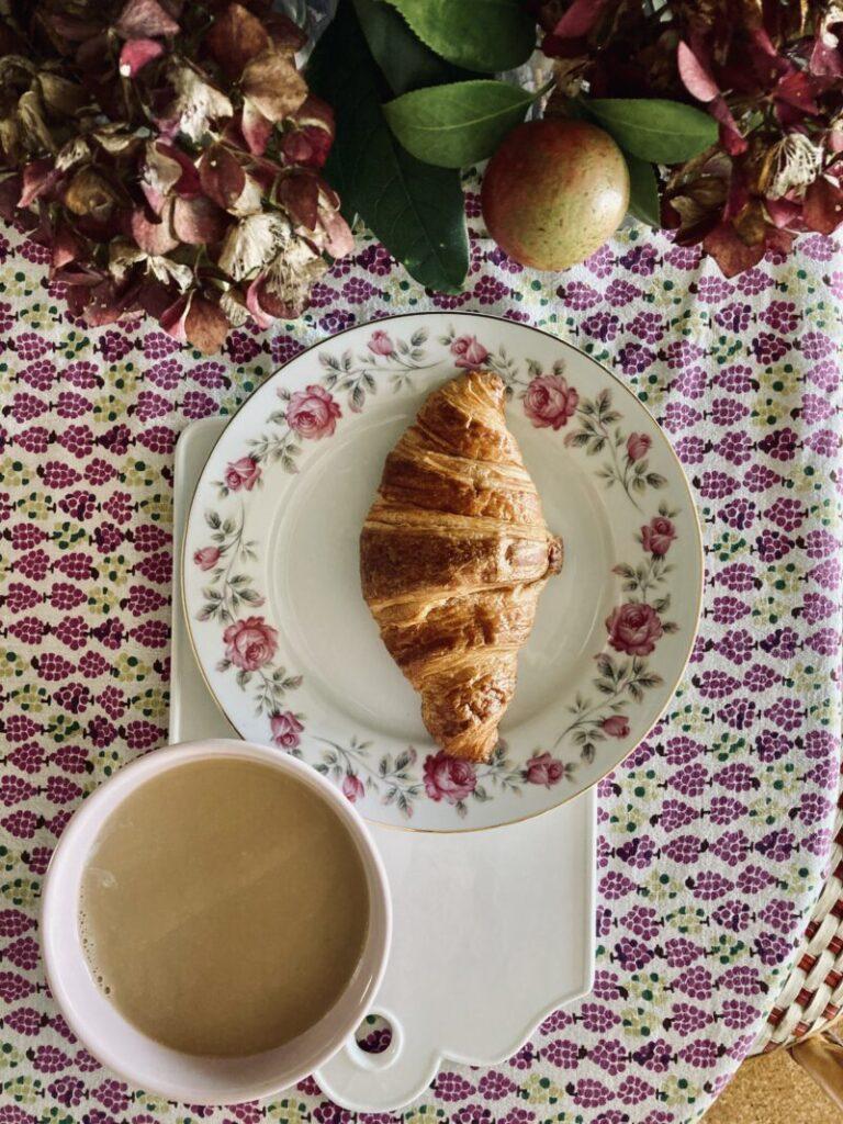 クロワッサンとピンクのカフェオレボウルに入ったカフェオレ